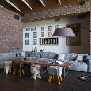 Ejemplo de salón para visitas tipo loft, actual, extra grande, con paredes marrones, suelo laminado, chimenea de doble cara, marco de chimenea de ladrillo, televisor independiente y suelo marrón