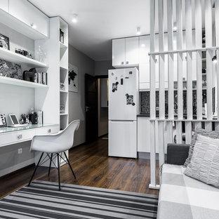 На фото: маленькая открытая гостиная комната в современном стиле с полом из ламината, коричневым полом и серыми стенами с