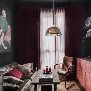 На фото: со средним бюджетом открытые гостиные комнаты среднего размера в стиле лофт с черными стенами и полом из ламината