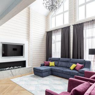 Пример оригинального дизайна: парадная, двухуровневая гостиная комната в современном стиле с бежевыми стенами, паркетным полом среднего тона, горизонтальным камином, телевизором на стене и коричневым полом