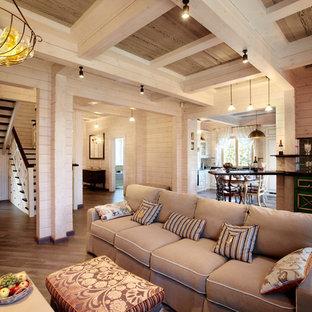 Modelo de salón con barra de bar abierto, tradicional renovado, grande, con paredes beige, suelo de madera en tonos medios, chimenea de esquina, marco de chimenea de piedra, televisor colgado en la pared y suelo marrón
