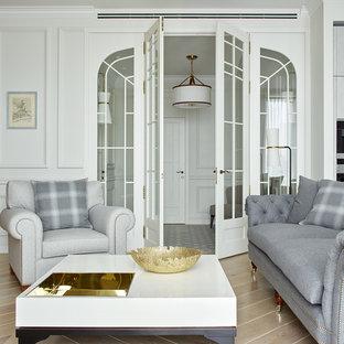 На фото: открытая гостиная комната в стиле современная классика с белыми стенами, светлым паркетным полом и бежевым полом