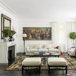 Пример оригинального дизайна: парадная гостиная комната в классическом стиле с белыми стенами, темным паркетным полом, стандартным камином и фасадом камина из камня