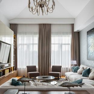 Свежая идея для дизайна: гостиная комната в современном стиле с белыми стенами, паркетным полом среднего тона, мультимедийным центром, коричневым полом и сводчатым потолком - отличное фото интерьера