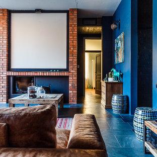 Inspiration för stora eklektiska allrum med öppen planlösning, med ett bibliotek, blå väggar, skiffergolv, en bred öppen spis, en spiselkrans i tegelsten och en väggmonterad TV