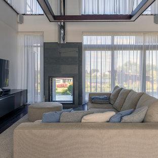 На фото: парадные, открытые гостиные комнаты в современном стиле с белыми стенами, двусторонним камином и фасадом камина из камня