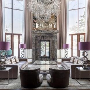 Идея дизайна: огромная парадная гостиная комната в современном стиле с бежевыми стенами, двусторонним камином и фасадом камина из камня