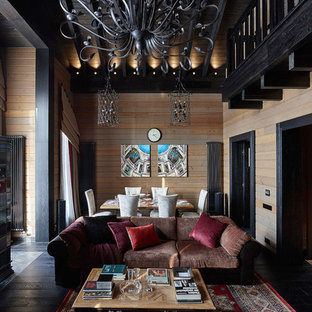 This is an example of a country open concept living room in Moscow with brown walls, dark hardwood floors and black floor.