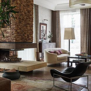 Свежая идея для дизайна: парадная гостиная комната в стиле современная классика с паркетным полом среднего тона, двусторонним камином, бежевыми стенами, фасадом камина из кирпича и коричневым полом - отличное фото интерьера