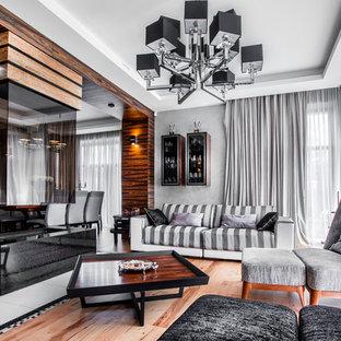 Идея дизайна: парадная, открытая гостиная комната в стиле современная классика с серыми стенами, паркетным полом среднего тона, двусторонним камином и коричневым полом