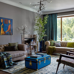 На фото: открытая гостиная комната в стиле фьюжн с домашним баром, серыми стенами, стандартным камином и фасадом камина из металла без ТВ с