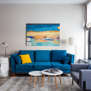 Пример оригинального дизайна: открытая гостиная комната среднего размера в современном стиле с бежевыми стенами, паркетным полом среднего тона, телевизором на стене и коричневым полом без камина