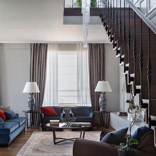 На фото: гостиная комната в стиле современная классика с серыми стенами, темным паркетным полом, стандартным камином и коричневым полом с