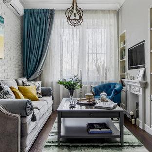 Пример оригинального дизайна: гостиная комната в классическом стиле с серыми стенами, темным паркетным полом, телевизором на стене, коричневым полом и кирпичными стенами