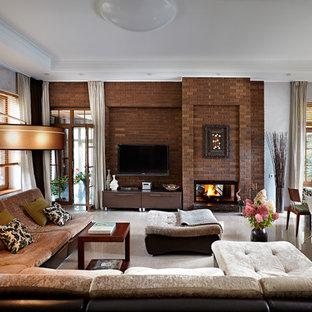 Modelo de salón para visitas abierto, tradicional renovado, grande, con suelo de baldosas de porcelana, chimenea de doble cara, televisor colgado en la pared, marco de chimenea de ladrillo y paredes marrones