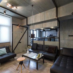 Пример оригинального дизайна интерьера: маленькая парадная, открытая гостиная комната в стиле лофт с полом из керамической плитки, телевизором на стене, серым полом и серыми стенами