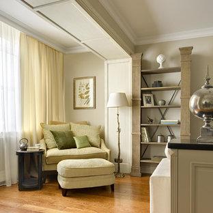 Esempio di un soggiorno classico di medie dimensioni con libreria, pareti beige e pavimento in legno massello medio