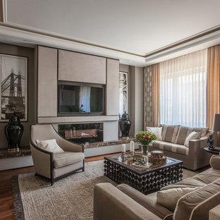 Пример оригинального дизайна: парадная, открытая гостиная комната в стиле современная классика с бежевыми стенами, паркетным полом среднего тона, стандартным камином, телевизором на стене и коричневым полом