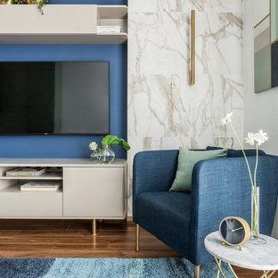 Idéer för ett litet modernt allrum med öppen planlösning, med blå väggar, laminatgolv, en väggmonterad TV och brunt golv