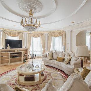 Стильный дизайн: гостиная комната в классическом стиле с белыми стенами, светлым паркетным полом, отдельно стоящим ТВ и коричневым полом без камина - последний тренд