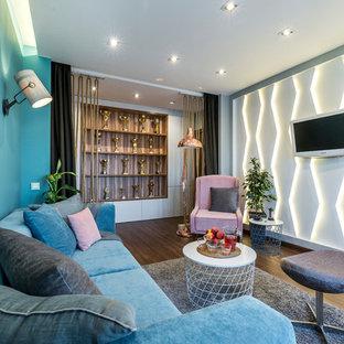 Неиссякаемый источник вдохновения для домашнего уюта: изолированная гостиная комната в современном стиле с синими стенами, паркетным полом среднего тона и телевизором на стене