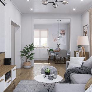 Modelo de salón abierto, nórdico, de tamaño medio, con paredes blancas, televisor colgado en la pared, suelo marrón y suelo laminado