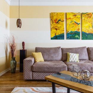 Стильный дизайн: изолированная гостиная комната в современном стиле с желтыми стенами и коричневым полом - последний тренд