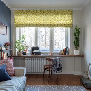 На фото: маленькая изолированная гостиная комната в стиле ретро с синими стенами, паркетным полом среднего тона и коричневым полом без камина, ТВ