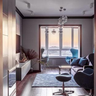 Immagine di un soggiorno minimal di medie dimensioni e chiuso con libreria, pareti grigie, pavimento in laminato, camino lineare Ribbon, cornice del camino in metallo, TV a parete, pavimento marrone e carta da parati