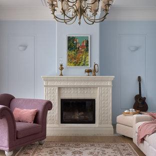 На фото: гостиная комната в классическом стиле с синими стенами, стандартным камином и фасадом камина из плитки с