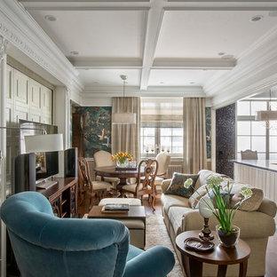 На фото: большая парадная, открытая гостиная комната в викторианском стиле с зелеными стенами, темным паркетным полом, отдельно стоящим ТВ и коричневым полом с