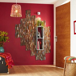 Bild på ett funkis allrum med öppen planlösning, med röda väggar och ljust trägolv
