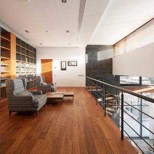 Идея дизайна: большая двухуровневая гостиная комната в современном стиле с библиотекой, разноцветными стенами, подвесным камином, фасадом камина из металла, паркетным полом среднего тона и коричневым полом
