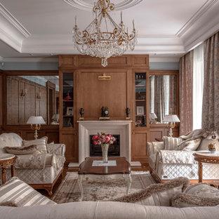На фото: парадная гостиная комната в классическом стиле с стандартным камином, многоуровневым потолком и панелями на части стены