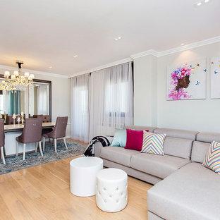 Modelo de salón para visitas abierto, ecléctico, de tamaño medio, sin chimenea, con paredes beige y suelo de madera clara