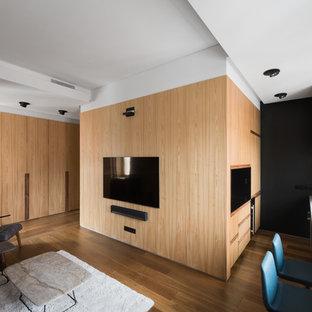 Свежая идея для дизайна: маленькая открытая гостиная комната в современном стиле с коричневыми стенами, паркетным полом среднего тона, телевизором на стене и коричневым полом - отличное фото интерьера