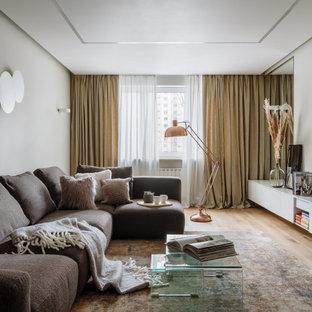 Свежая идея для дизайна: изолированная гостиная комната среднего размера в современном стиле с бежевыми стенами, светлым паркетным полом, бежевым полом и телевизором на стене - отличное фото интерьера