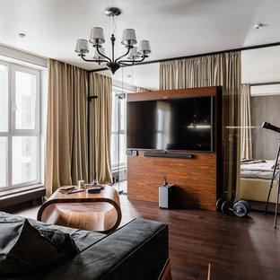 Свежая идея для дизайна: гостиная комната в современном стиле с серыми стенами, темным паркетным полом, телевизором на стене и коричневым полом - отличное фото интерьера