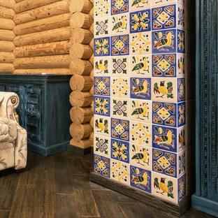 他の地域の中くらいのラスティックスタイルのおしゃれな独立型ファミリールーム (マルチカラーの壁、濃色無垢フローリング、内蔵型テレビ、茶色い床) の写真