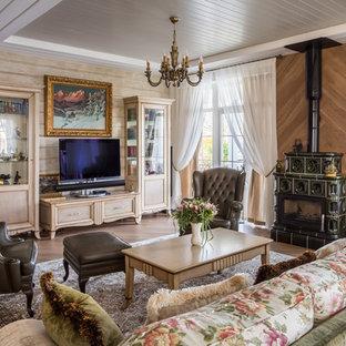 На фото: большая гостиная комната в классическом стиле с бежевыми стенами, печью-буржуйкой и коричневым полом с