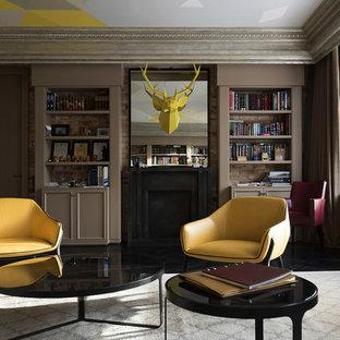 Свежая идея для дизайна: изолированная гостиная комната в стиле современная классика с библиотекой, бежевыми стенами, стандартным камином и черным полом - отличное фото интерьера