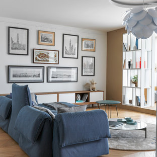 Новый формат декора квартиры: открытая гостиная комната в современном стиле с белыми стенами, бежевым полом и паркетным полом среднего тона