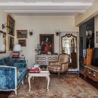 На фото: гостиная комната в классическом стиле с бежевыми стенами, темным паркетным полом, отдельно стоящим ТВ и коричневым полом с