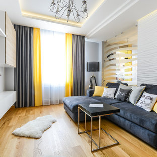 Создайте стильный интерьер: изолированная гостиная комната среднего размера в современном стиле с паркетным полом среднего тона, телевизором на стене и белыми стенами - последний тренд