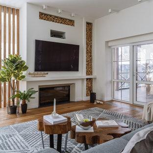 Стильный дизайн: большая парадная, открытая гостиная комната в скандинавском стиле с белыми стенами, паркетным полом среднего тона, стандартным камином, фасадом камина из штукатурки, телевизором на стене и коричневым полом - последний тренд
