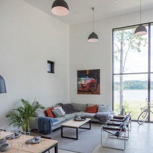 На фото: парадная, открытая гостиная комната в стиле лофт с белыми стенами, бетонным полом и серым полом с