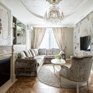 Стильный дизайн: гостиная комната в классическом стиле с паркетным полом среднего тона, стандартным камином, фасадом камина из камня, телевизором на стене и коричневым полом - последний тренд