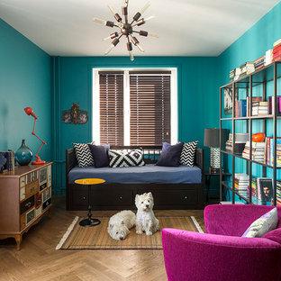 Imagen de sala de estar con biblioteca ecléctica con paredes azules y suelo de madera en tonos medios
