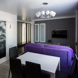 Modern inredning av ett litet vardagsrum, med vita väggar, laminatgolv, en väggmonterad TV och grått golv
