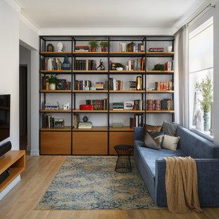 Новые идеи обустройства дома: изолированная гостиная комната в современном стиле с библиотекой, светлым паркетным полом, телевизором на стене, синими стенами и коричневым полом